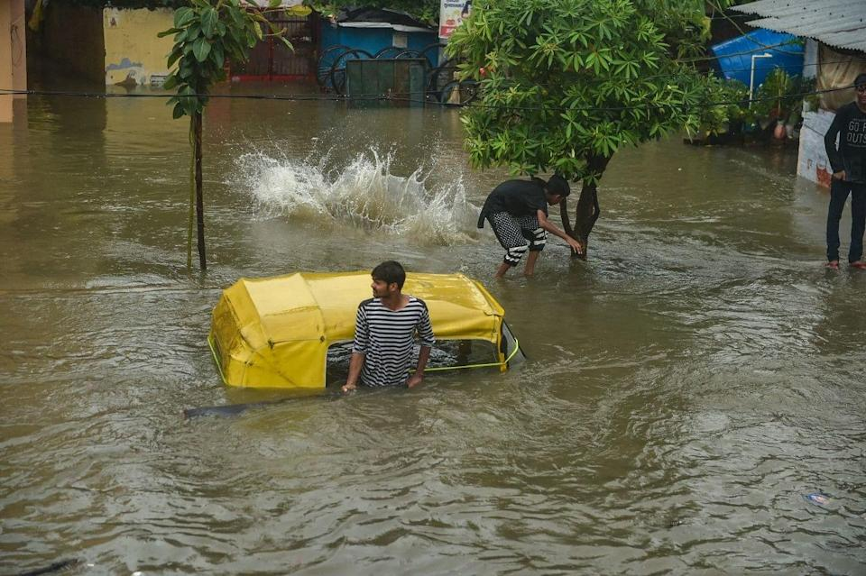 """<div class=""""paragraphs""""><p>Lucknow: A man stands near a partially submerged auto rickshaw due to waterlogging following heavy rains.</p></div>"""