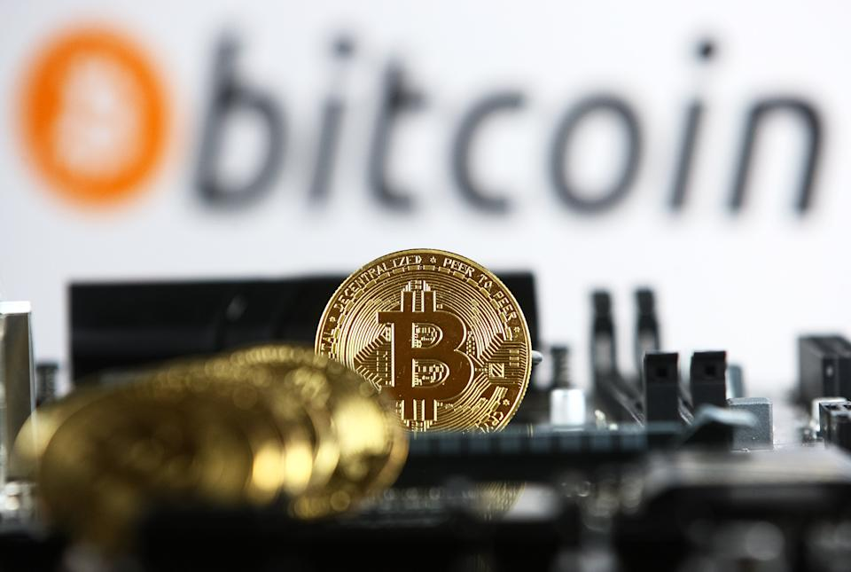 Bitcoin cryptocurrency coins and a PC motherboard are pictured in Kyiv on 19 July, 2021.  (Photo by STR/NurPhoto via Getty Images)