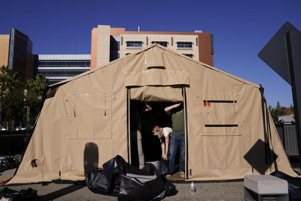 Volunteers help set up a mobile field hospital at UCI Medical Center, Monday, Dec. 21, 2020, in Orange, Calif. California's overwhelmed hospitals are setting up makeshift extra beds for coronavirus patients, and a handful of facilities in hard-hit Los Angeles County are drawing up emergency plans in case they have to limit how many people receive life-saving care. (AP Photo/Jae C. Hong)