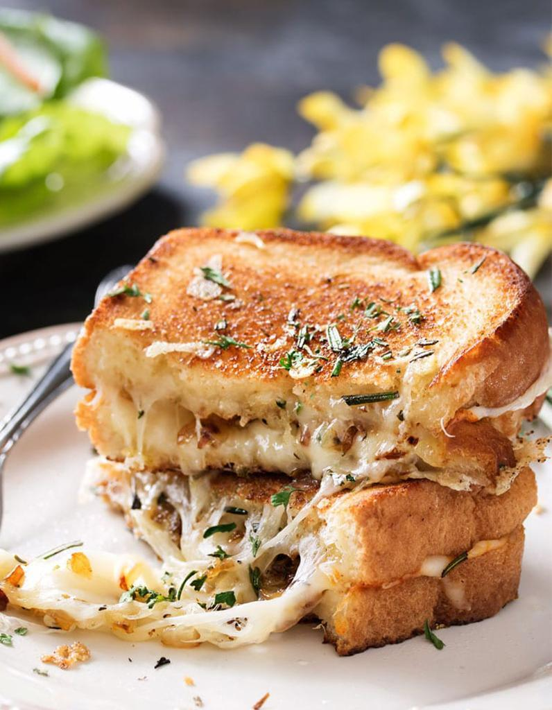 """<p>Le bon mix : pain + mayonnaise + gruyère + cheddar + munster + oignons + romarin + thym </p><p>Découvrir la recette <a href=""""https://www.thechunkychef.com/ultimate-gourmet-grilled-cheese/"""" rel=""""nofollow noopener"""" target=""""_blank"""" data-ylk=""""slk:ici"""" class=""""link rapid-noclick-resp"""">ici</a></p><br>"""