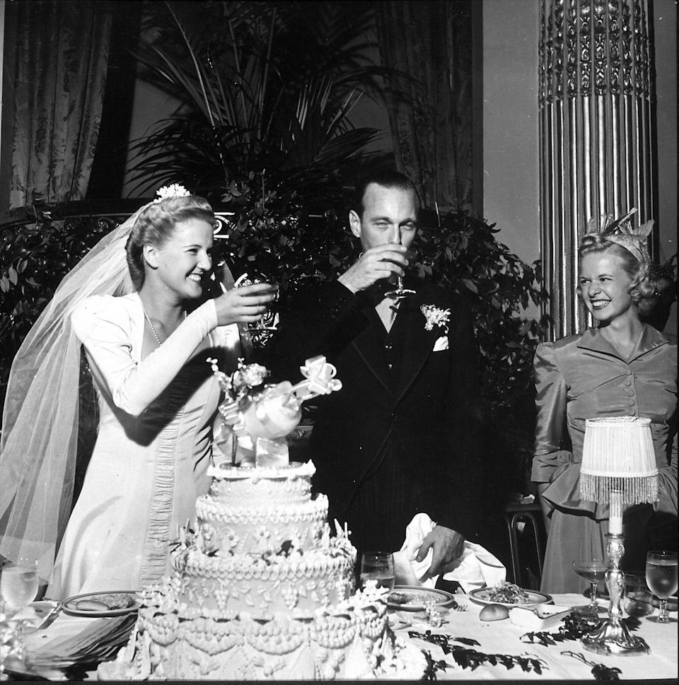 """<p>A just-married couple (circa 1941) raises a glass in celebration. Another on-trend bride for her time, she wears a very tailored dress complete with strong shoulders. </p><p><a href=""""http://www.goodhousekeeping.com/life/news/a42183/funny-wedding-rsvp-cards/"""" rel=""""nofollow noopener"""" target=""""_blank"""" data-ylk=""""slk:Take a look at hilarious RSVP cards »"""" class=""""link rapid-noclick-resp""""><em>Take a look at hilarious RSVP cards »</em></a></p>"""
