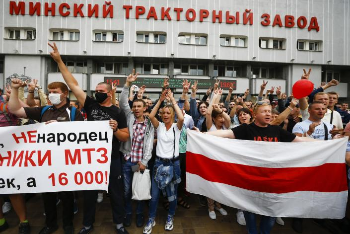 """Workers hold an old Belarusian national flag and a banner reading """"we are not cattle, we are not sheep, we are workers of MTZ, we are not 20 people, we are 16,000"""" during a rally in front of the main entrance of the Minsk Tractor Works Plant in Minsk, Belarus, Friday, Aug. 14, 2020. Workers at the plant demanded a new election and called for the release of all those who were detained in a brutal police crackdown on demonstrators challenging the official results of Sunday's presidential vote. (AP Photo/Sergei Grits)"""