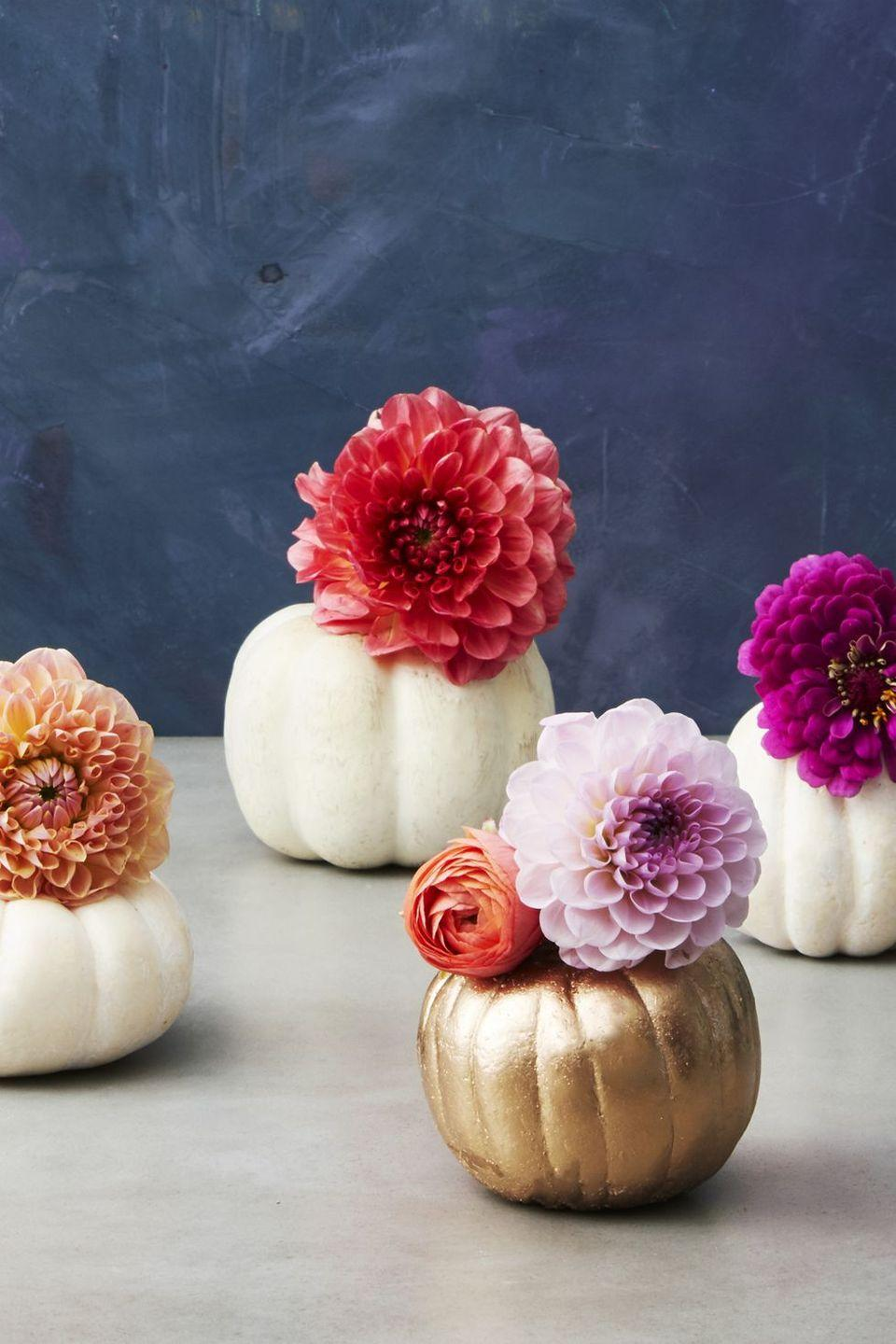 <p>Turn mini pumpkins into pots to show off your favorite blooms, like dahlias, ranunculuses, and mums. To make them, carve your mini pumpkins as you normally would. Then, cut the bottom of a water bottle and slide them right inside the pumpkins, so they function as vases. </p>