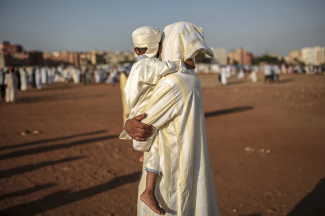 <p>A father holds his son as they attend Eid al-Adha prayers in Sale, north of Rabat, Morocco, Friday, Sept. 1, 2017. (Photo: Mosa'ab Elshamy/AP) </p>
