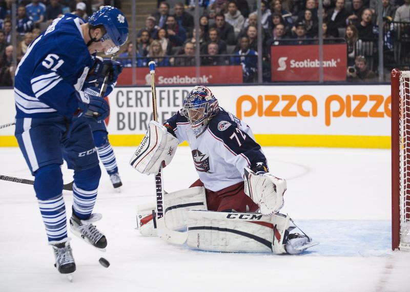 Toronto Maple Leafs' Jake Gardiner stumbles over the puck as Columbus Blue Jackets goalie Sergei Bobrovski keeps his eye on it during the second period of an NHL hockey game in Toronto on Monday, Nov. 25, 2013. (AP Photo/The Canadian Press, Aaron Vincent Elkaim)
