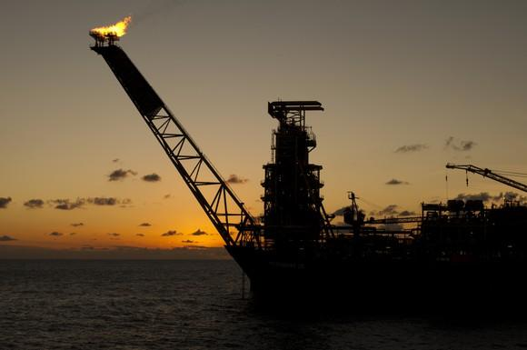 Silhouette of floating production, storage, and offloading vessel with sun setting in the background