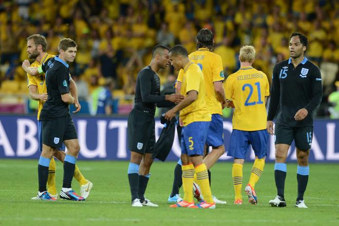 Swedish defender Olof Mellberg (L) embraces English midfielder Steven Gerrard (2ndL) at the end of the Euro 2012 championships football match Sweden vs England on June 15, 2012 at the Olympic Stadium in Kiev. Englan won 3-2.  AFP PHOTO / CARL DE SOUZACARL DE SOUZA/AFP/GettyImages