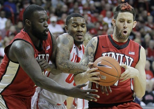 UNLV's Brice Massamba, left, and Chace Stanback, right, battle for a rebound against New Mexico's Demetrius Walker in the first half of a semifinal NCAA college basketball game during the Mountain West Conference tournament, Friday, March 9, 2012, in Las Vegas. (AP Photo/Julie Jacobson)