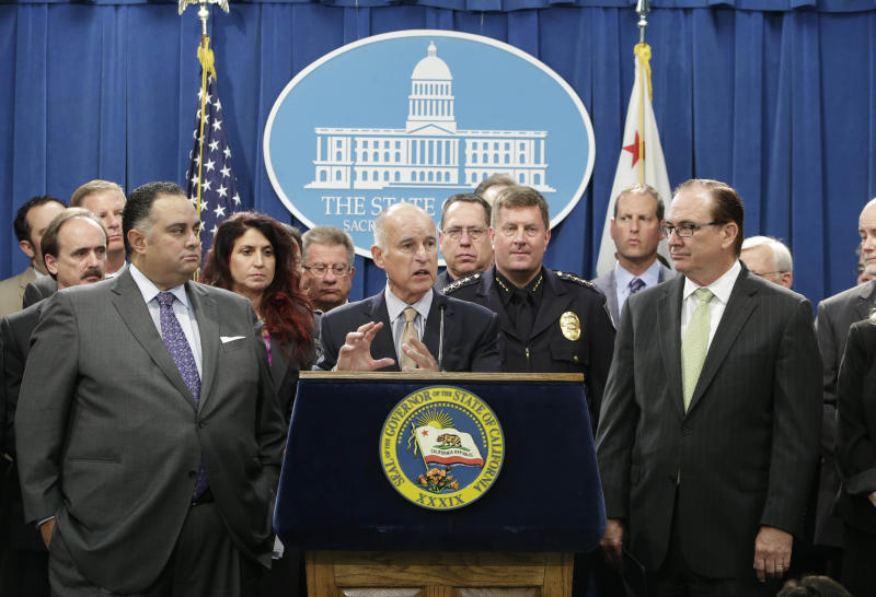Gov. Jerry Brown, center, discusses a proposal to reduce California's prison population, at a Capitol news conference in Sacramento, Calif., Tuesday, Aug. 27, 2013. In response to a federal court order to reduce the state's prison population, Brown announced a $315 million plan to send thousands of inmates to private prisons and to empty county jail cells to avoid what he and his supporters say would be a mass release of dangerous felons. Brown was joined Assembly Speaker John Perez, D-Los Angeles, left, Senate Minority Leader Bob Huff, of Diamond Bar, right, and various of law enforcement leaders, local government officials, and victims rights advocates. (AP Photo/Rich Pedroncelli)