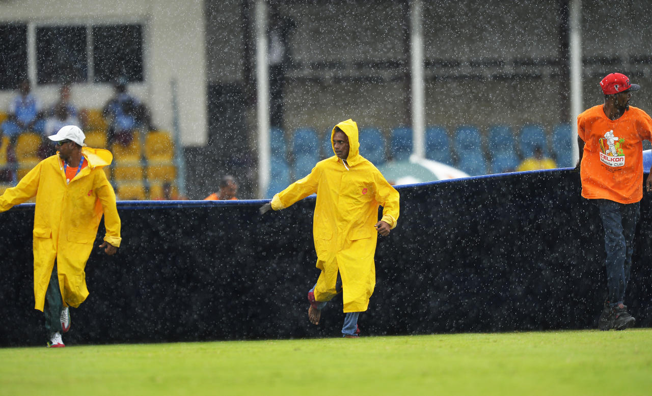 Groundsmen pull a plastic sheet to cover the field as rain interrupts the fifth match of the Tri-Nation series between Sri Lanka and West Indies at the Queen's Park Oval in Port of Spain on July 7, 2013. West Indies won the toss and elected to field. AFP PHOTO/Jewel Samad