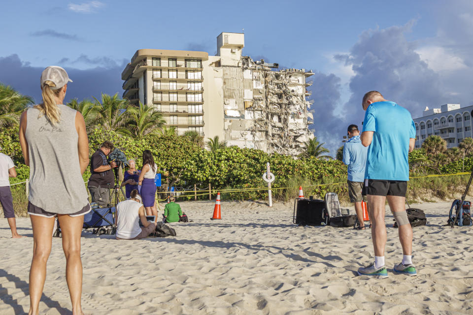 People stand on the beach looking at the collapsed Champlain Towers South in Surfside.