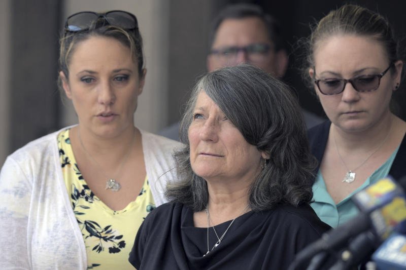 Surrounded by family and friends, Debra Sorrells, the mother of Baltimore County Police Officer Amy Caprio, gazes skyward following the life sentence for her daughter's death, meted out for 17-year-old Dawnta Harris at Baltimore County Circuit Court Wednesday, Aug. 21, 2019, in Towson, Md. Harris was tried as an adult earlier this year and convicted of felony murder in the slaying of Officer Caprio. (Karl Merton Ferron/The Baltimore Sun via AP)