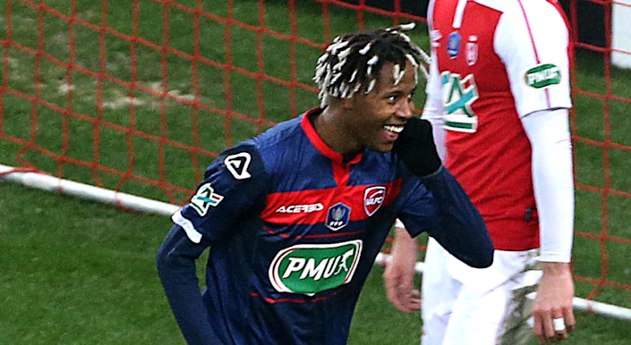 A soccer player in Valenciennes uniform smiles.