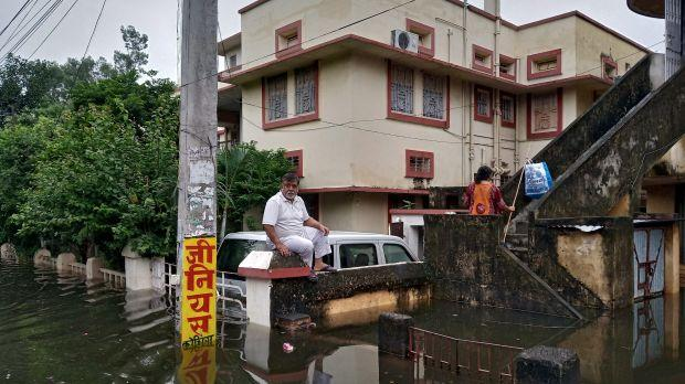 A man sits on a boundary wall of a house during floods in Bihar