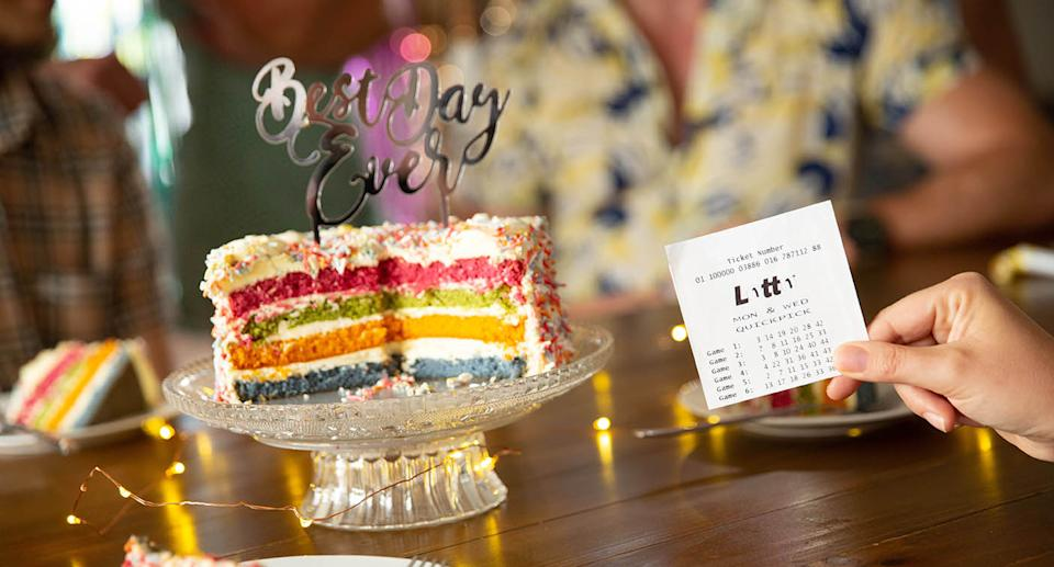 Someone celebrating finding out they have a winning Lotto ticket near a colourful cake.