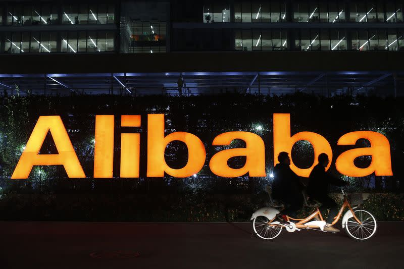 People ride a double bicycle past a logo of The Alibaba Group at the company's headquarters on the outskirts of Hangzhou