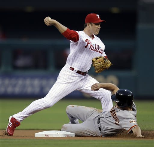 Philadelphia Phillies second baseman Chase Utley, top, forces out San Francisco Giants' Ryan Theriot at second on a fielders choice by Melky Cabrera in the first inning of a baseball game, Friday, July 20, 2012, in Philadelphia. Cabrera was safe at first on the play. (AP Photo/Brynn Anderson)