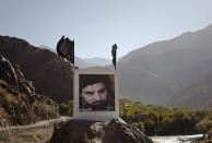 FILE - In this Sept 28, 2011 file photo, a large poster of late charismatic guerrilla fighter Ahmad Shah Massoud is displayed next to a road leading into the Panjshir Valley. In August 2021, the last remnants of Afghanistan's shattered security forces have vowed to resist the Taliban in the remote Panjshir Valley north of Kabul, that has defied conquerors before. Under the leadership of Massoud, fighters in the Panjshir Valley held off the Soviets in the 1980s and the Taliban a decade later. Any attempt to re-enact his exploits appears likely to fail, posing little threat to the country's new Taliban rulers. (AP Photo/Anja Niedringhaus, File)