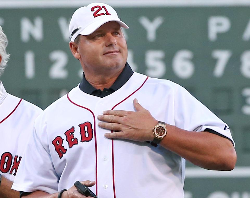 Former Boston Red Sox pitcher Roger Clemens pats his chest to cheering fans during a ceremony prior to a baseball game between the Red Sox and the Seattle Mariners at Fenway Park in Boston on Tuesday, July 30, 2013. The Red Sox are celebrating the 25th anniversary of a streak in 1988 that began after Joe Morgan became manager of the team. (AP Photo/Elise Amendola)