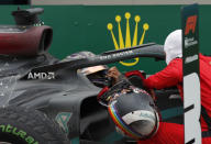 Mercedes driver Lewis Hamilton of Britain, left, is congratulated by Ferrari driver Sebastian Vettel of Germany after winning the race and the world championship after the Turkish Formula One Grand Prix at the Istanbul Park circuit racetrack in Istanbul, Sunday, Nov. 15, 2020. (Murad Sezer/Pool via AP)