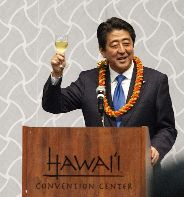 Japanese Prime Minister Shinzo Abe offers a toasts to guests at a dinner held in Abe's honor, Monday, Dec. 26, 2016, in Honolulu. Abe laid wreaths at various cemeteries and memorials Monday ahead of a visit to the site of the 1941 bombing that plunged the United States into World War II. The USS Arizona Memorial at Pearl Harbor will be closed to the public Tuesday when Abe visits the historic site, joined by U.S. President Barack Obama, who is vacationing in Hawaii with his family. (AP Photo/Marco Garcia)