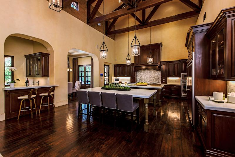 The kitchen boasts dark wood cabinets and high ceilings.
