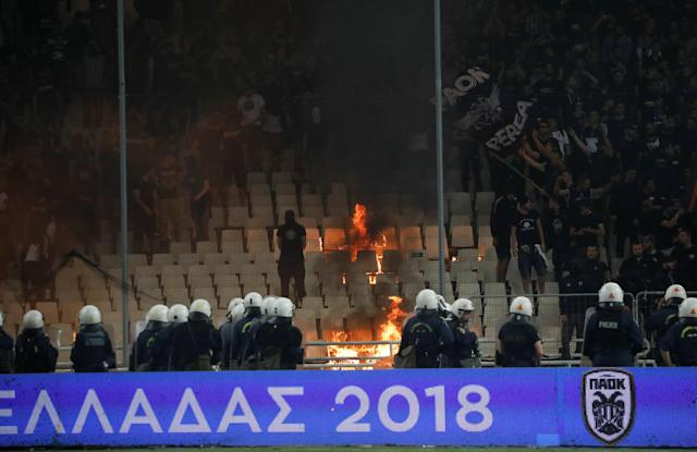 Soccer Football - Greek Cup Final - AEK Athens vs PAOK Salonika - Athens Olympic Stadium, Athens, Greece - May 12, 2018 Police and fans look on as a fire starts in the stands REUTERS/Alkis Konstantinidis