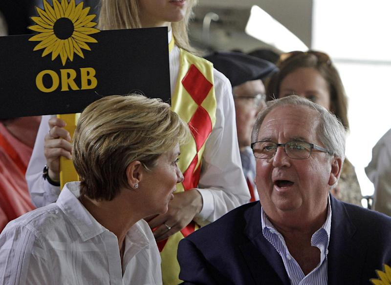 """Orb's trainer Claude R. """"Shug"""" McGaughey, right, talks with his wife Alison before the start of the Preakness Stakes post position draw at Pimlico Race Course in Baltimore, Wednesday, May 15, 2013. Despite getting the inside post in Wednesday's draw, Orb was made an even-money favorite to win the Preakness and keep alive his bid to become horse racing's first Triple Crown winner since Affirmed in 1978. (AP Photo/Garry Jones)"""