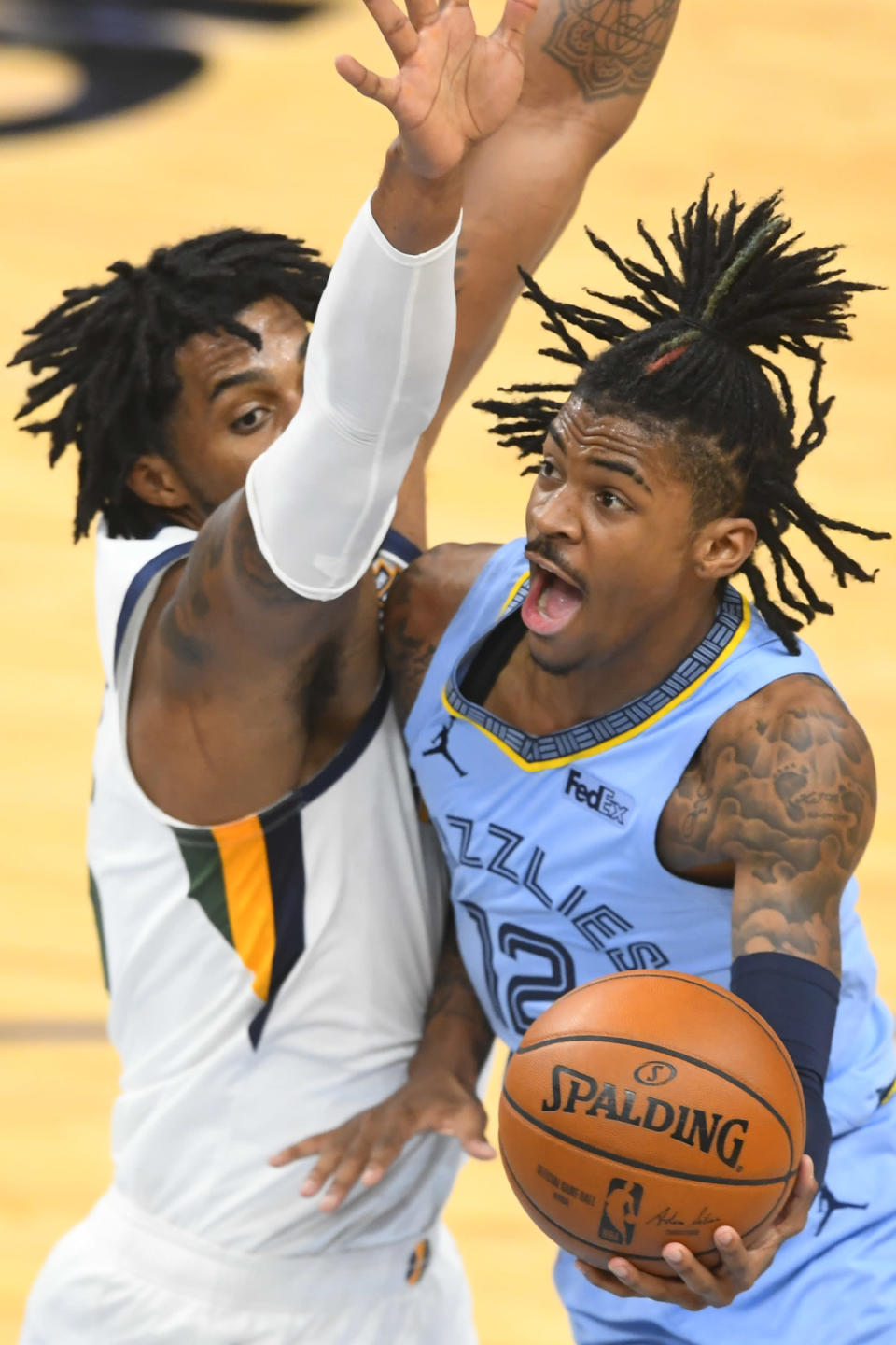 Memphis Grizzlies guard Ja Morant (12) goes to the basket as Utah Jazz center Derrick Favors defends during the first half of Game 3 of an NBA basketball first-round playoff series Saturday, May 29, 2021, in Memphis, Tenn. (AP Photo/John Amis)
