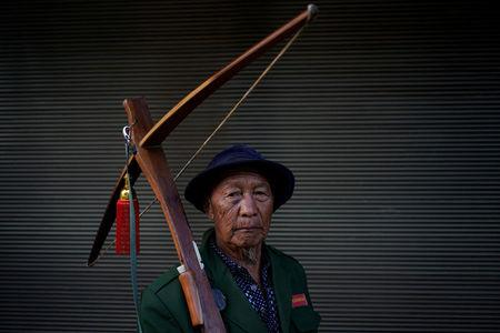 An ethnic Lisu man carries his crossbow as he poses for a photograph during a crossbow shooting competition in Luzhang township of Nujiang Lisu Autonomous Prefecture in Yunnan province, China, March 29, 2018. REUTERS/Aly Song