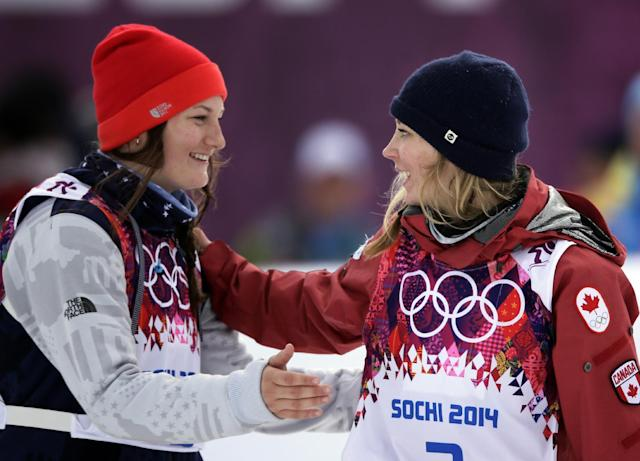 Canada's Dara Howell, right, celebrates with silver medalist Devin Logan of the United States after Howell took the gold medal in the women's freestyle skiing slopestyle final at the Rosa Khutor Extreme Park at the 2014 Winter Olympics, Tuesday, Feb. 11, 2014, in Krasnaya Polyana, Russia. (AP Photo/Jae C. Hong)