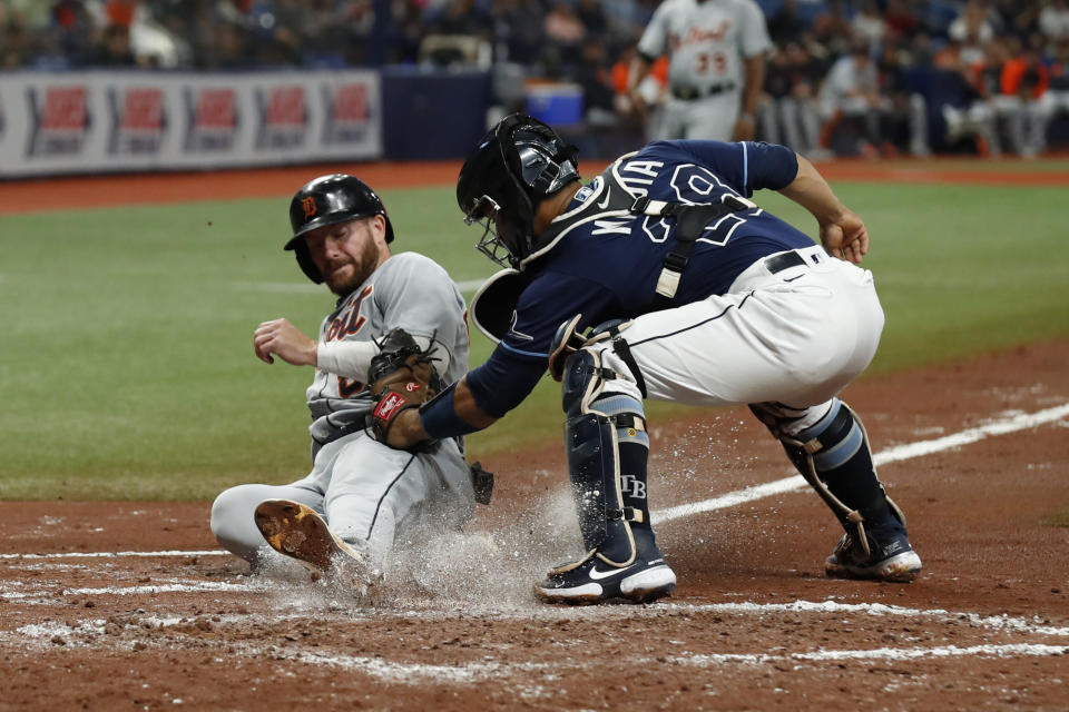 Detroit Tigers' Robbie Grossman, left, beats the tag of Tampa Bay Rays catcher Francisco Mejia while sliding safely home during the third inning of a baseball game Friday, Sept. 17, 2021, in St. Petersburg, Fla. (AP Photo/Scott Audette)