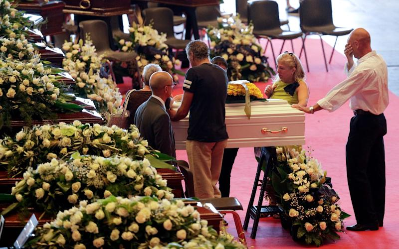 Relatives mourn at the coffin of a victim of the Genoa bridge collapse - AP