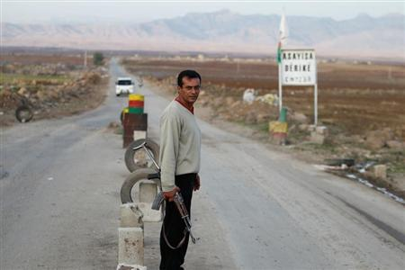 A Syrian Kurd Asaish stands at a security checkpoint at Derik in Al-Hasakah