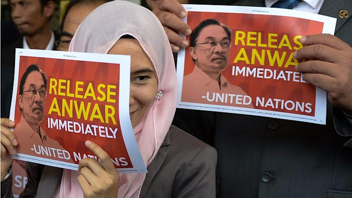Members of the Malaysian opposition parties hold signs reading 'Release Anwar immediately' in Kuala Lumpur in 2015