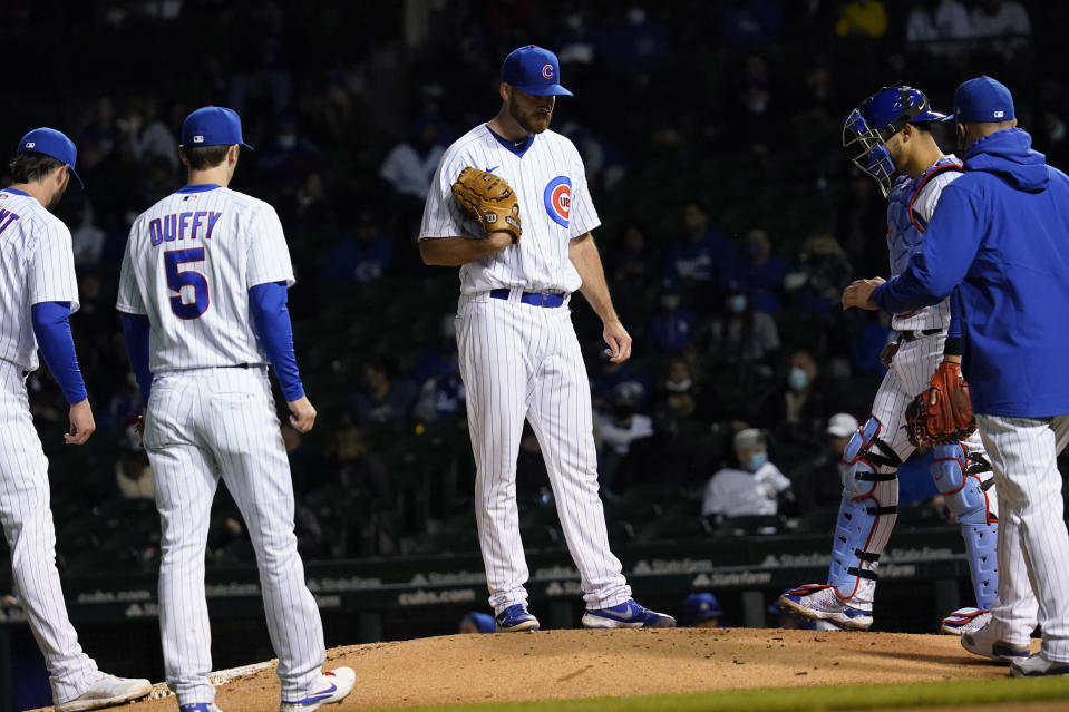 Chicago Cubs relief pitcher Kyle Ryan, center, reacts as he waits for manager David Ross, right, during the sixth inning of a baseball game against the Los Angeles Dodgers in Chicago, Wednesday, May 5, 2021. (AP Photo/Nam Y. Huh)