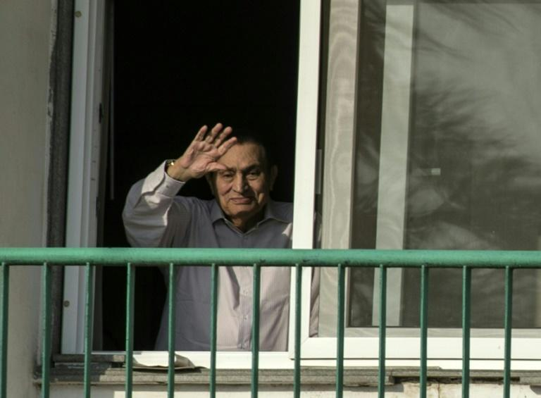 Former Egyptian president Hosni Mubarak waves to supporters from his room at the Maadi military hospital in Cairo on October 6, 2016