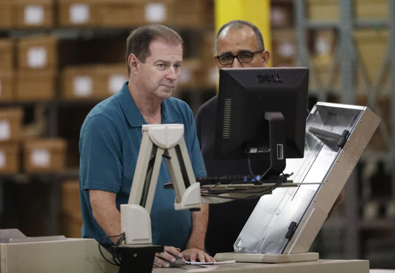 Employees at the Supervisor of Elections office prepare a machine during a recount, Thursday, Nov. 15, 2018, in West Palm Beach, Fla. (AP Photo/Wilfredo Lee)