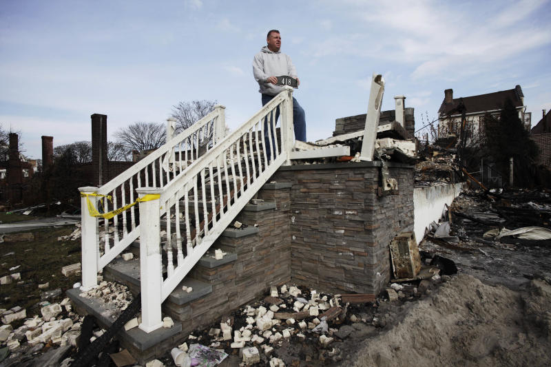 In this photo taken Sunday, Nov. 18, 2012, Ray Marten poses with the street number sign he recovered from the ashes of his fire-destroyed home in the Belle Harbor section of the Queens borough of New York. Several homes and businesses were destroyed by fire in the oceanside community during Superstorm Sandy. (AP Photo/Mark Lennihan)