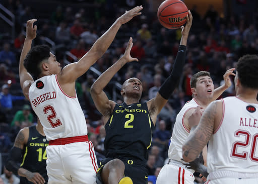 Oregon's Louis King, center, tries to shoot over Utah's Sedrick Barefield, left, during the second half of an NCAA college basketball game in the quarterfinals of the Pac-12 men's tournament Thursday, March 14, 2019, in Las Vegas. (AP Photo/John Locher)