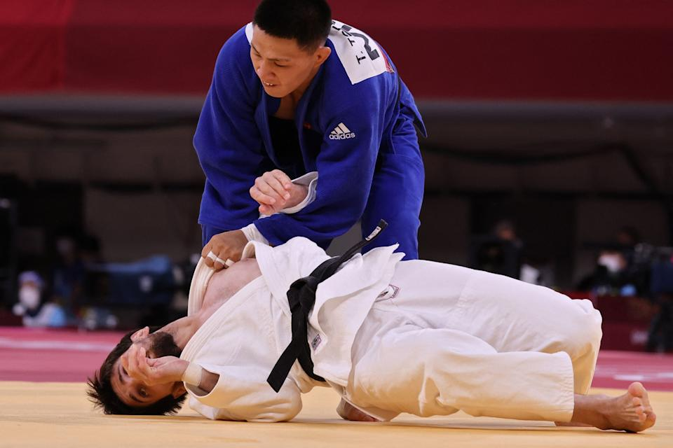 <p>Russia's Musa Mogushkov (white) and Mongolia's Tsogtbaatar Tsend-Ochir compete in the judo mixed team's quarterfinal bout during the Tokyo 2020 Olympic Games at the Nippon Budokan in Tokyo on July 31, 2021. (Photo by Jack GUEZ / AFP)</p>