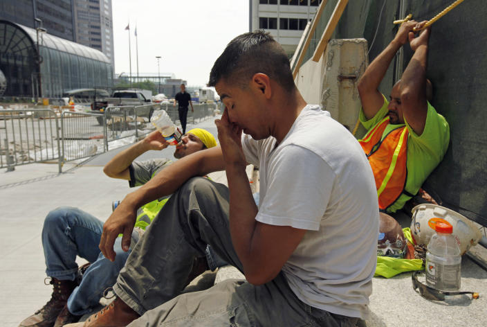 From left, construction workers Santiago Gomez, Jorge Moreno, Abel Lozano take a break from the extreme heat during a road construction project in downtown Chicago, Thursday, June 28, 2012. Temperatures in the city were expected to reach 96 Thursday with little relief expected in the next few days. (AP Photo/Sitthixay Ditthavong)