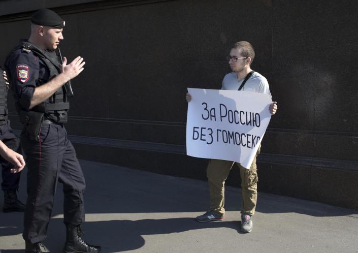 """A police officer speaks with a demonstrator near the State Duma, Russia's lower parliament chamber, in Moscow Tuesday, June 11, 2013. A controversial bill banning """"homosexual propaganda"""" is expected to be approved by Russia's lower house of parliament for the second and third of three hearings on Tuesday. Poster reads: """"For Russia without homosexuals."""" (AP Photo/Alexander Zemlianichenko)"""