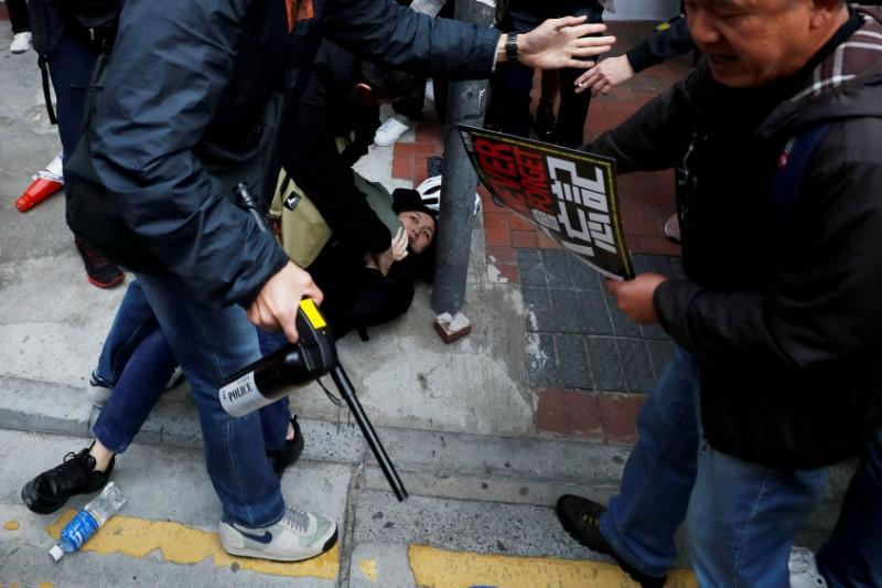 FILE PHOTO: A woman is detained by plainclothes police officers during an anti-government demonstration on New Year's Day, to call for better governance and democratic reforms in Hong Kong