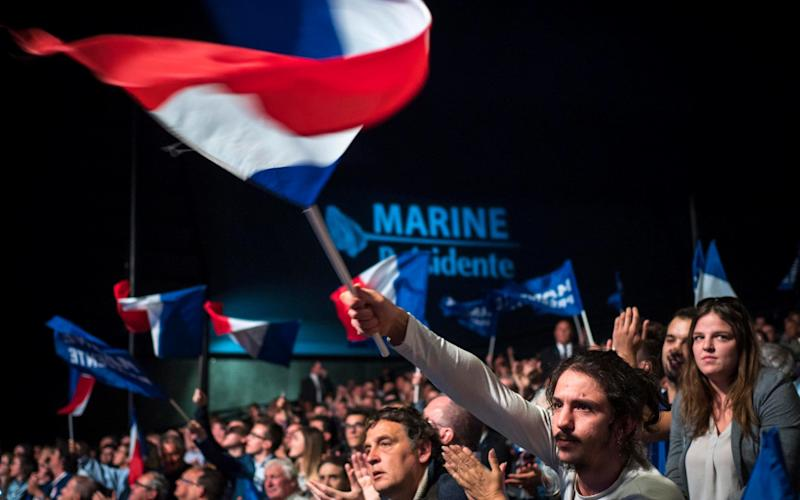 Man waves French tricolour in the crowd - Credit: Paul Durand/EPA
