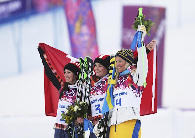 Women's ski cross gold medalist Marielle Thompson of Canada, center, celebrates with silver medalist and compatriot Kelsey Serwa, left, and bronze medalist Sweden's Anna Holmlund, right, at the Rosa Khutor Extreme Park, at the 2014 Winter Olympics, Friday, Feb. 21, 2014, in Krasnaya Polyana, Russia. (AP Photo/Sergei Grits)