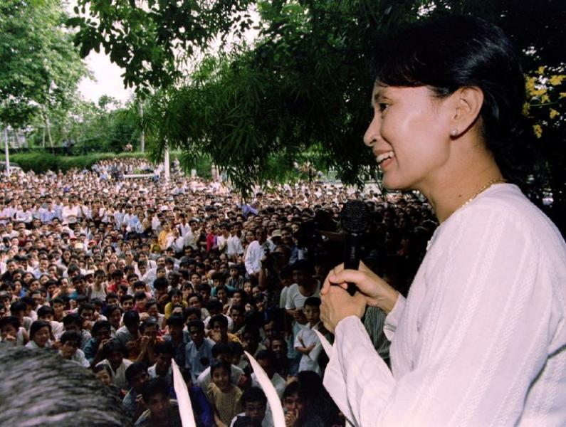 FILE PHOTO: Freed pro-democracry leader Aung San Suu Kyi smiles while speaking to hundreds of supporters from the gate at her residential compound in Yangon