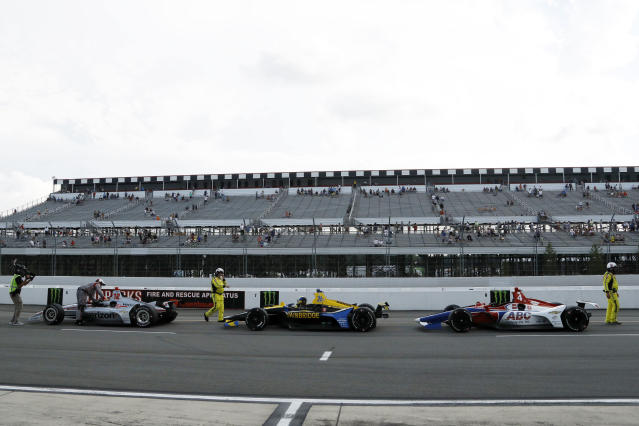 Drivers park on pit road as inclement weather delays an IndyCar Series auto race at Pocono Raceway, Sunday, Aug. 18, 2019, in Long Pond, Pa. (AP Photo/Matt Slocum)
