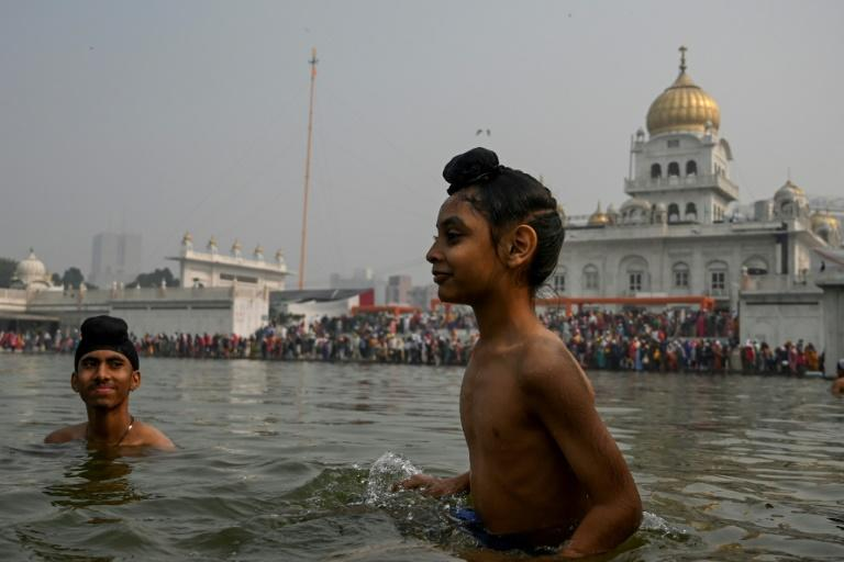 Young devotees take a holy dip on the occasion of the 550th birthday of Sikhism founder Guru Nanak