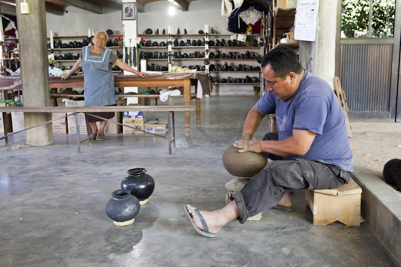 A man and woman at work making pottery in a Oaxacan pottery studio.